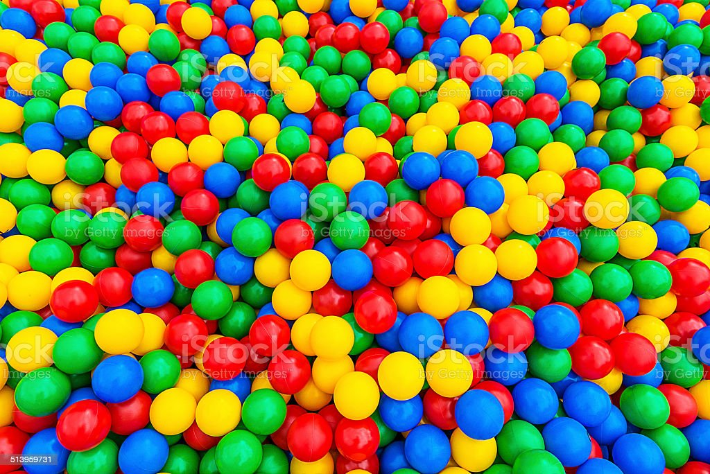 Ball pool with pile of green, blue, red, yellow balls stock photo