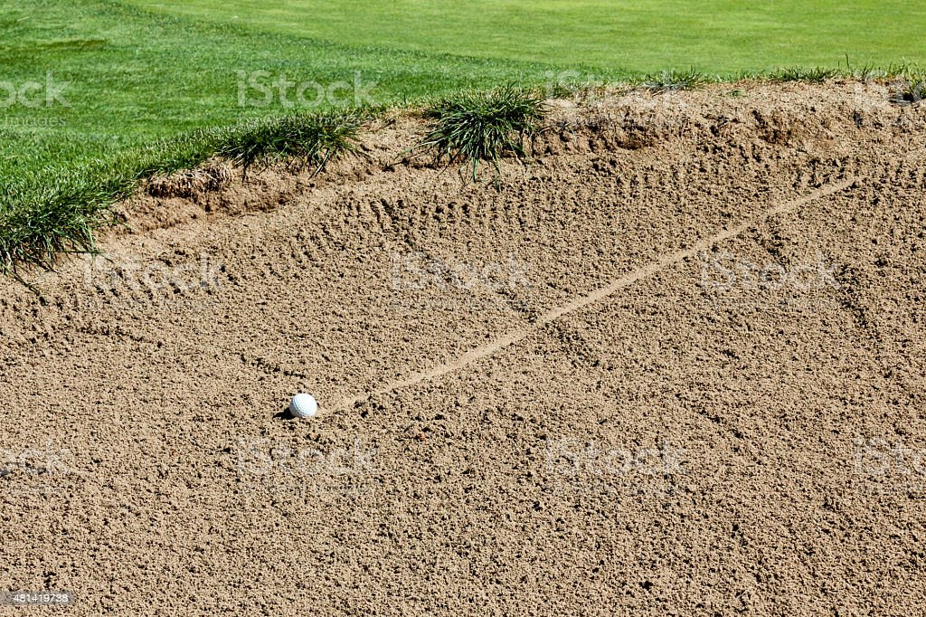 Ball rolling across a golf course sand trap stock photo