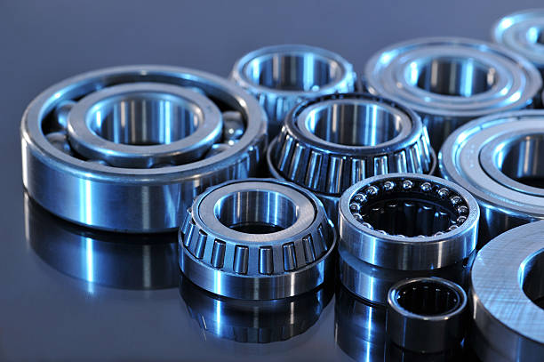 ball-bearings closeup view of several ball-bearings in blue light ball bearing stock pictures, royalty-free photos & images