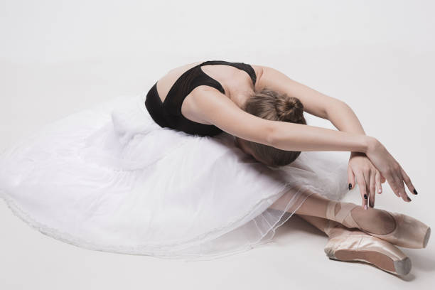 ballerina dancer sitting down with her legs crossed - dance group stock photos and pictures