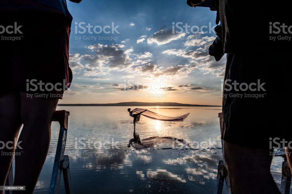Ballerina dancing on the lake at sunset and some photographers taken his stock photo