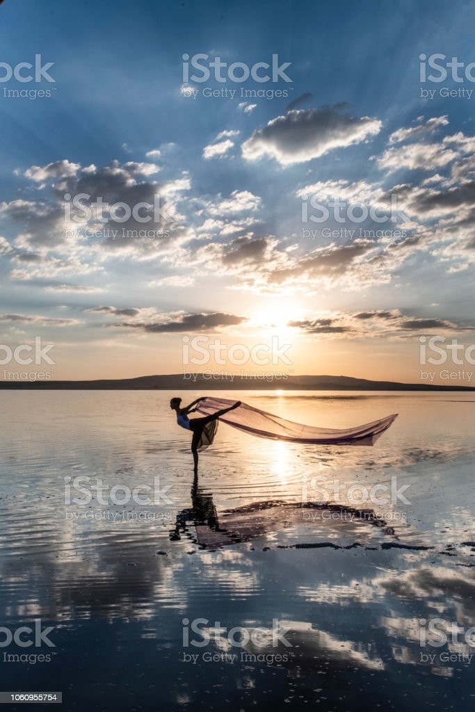 Ballerina dancing on the lake at sunset. stock photo