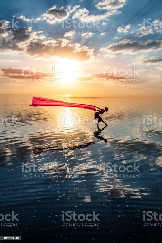 Ballerina dancing on the lake at sunset with red tulle. stock photo