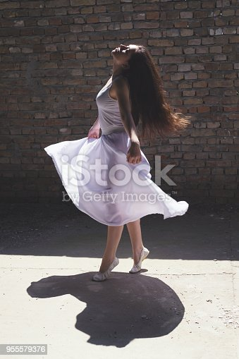 Ballerina in white dress dancing on the street on a sunny spring day.