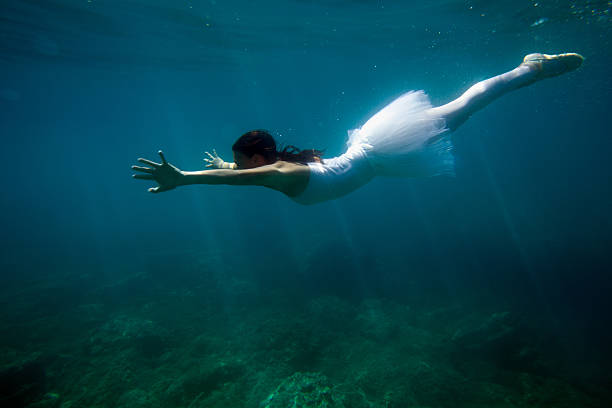 Ballerina dancing under the water Underwater shot of ballerina in white tutu and ballet slippers diving in the sea.You can see my other photos from Vetta collection: sun shining through dresses stock pictures, royalty-free photos & images
