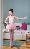 Cute  girl dreams of becoming a ballerina. She getting dressed and dancing in a domestic room.