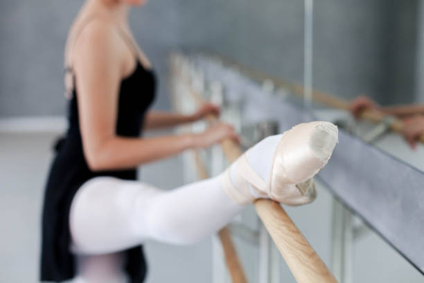Ballerina has dance workout in ballet class room. Girl is stretching with leg in pointe shoes on barre. Woman is doing exercises. stock photo