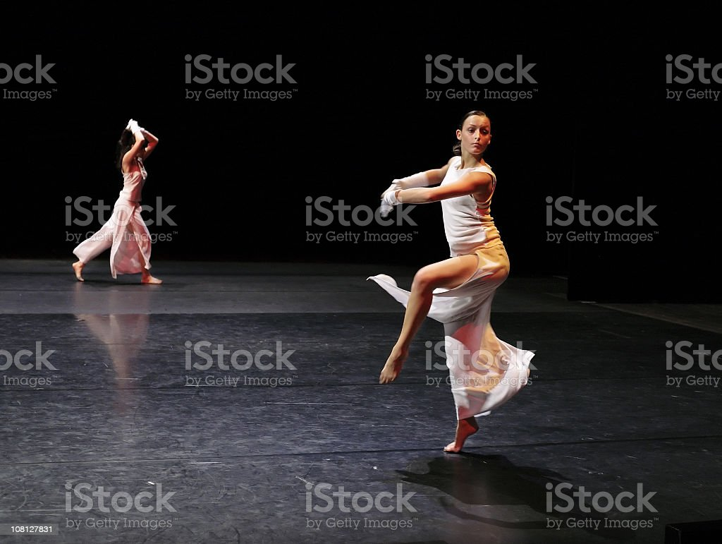 A Ballerina in White Executing a Pirouette stock photo