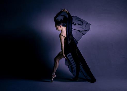 Beautiful ballerina in a beautiful black dress is dancing in a dark photostudio.