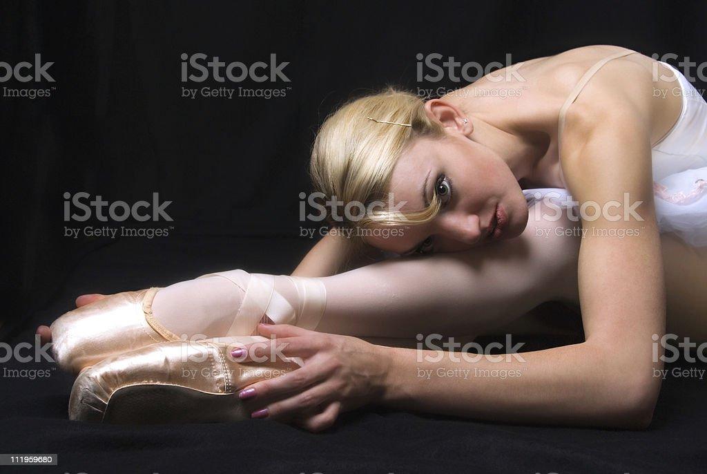 Ballerina leaning over her feet on black background stock photo