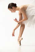 Ballerina posing in pointe shoes at gray floor