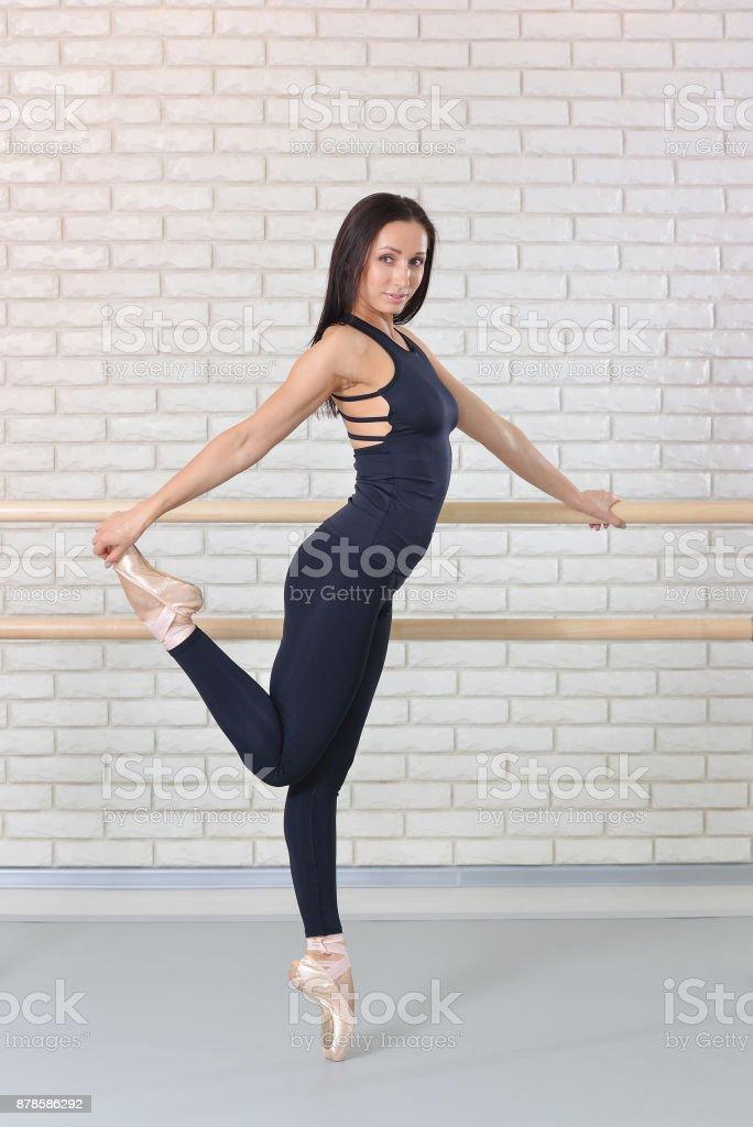 Bailarina posando junto a la barra en estudio de ballet, retrato de longitud completa de bailarina hermosa mujer mirando a cámara. - foto de stock