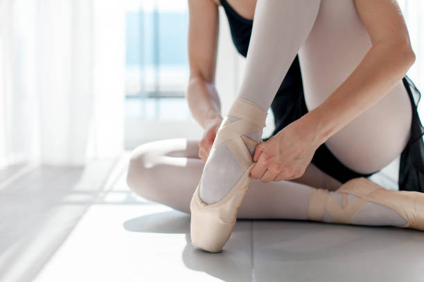 Ballerina puts on ballet pointe shoes. Girl is sitting on floor in sunny dance class room. Close up. stock photo