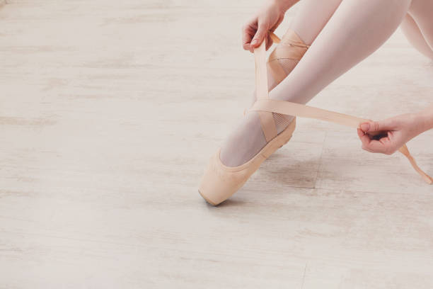 Ballerina puts on pointe ballet shoes, graceful legs stock photo