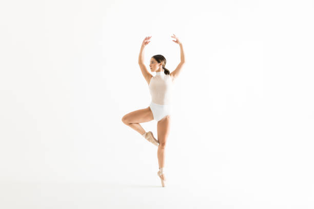 ballerina rehearsing on one leg with arms raised - leotard stock pictures, royalty-free photos & images