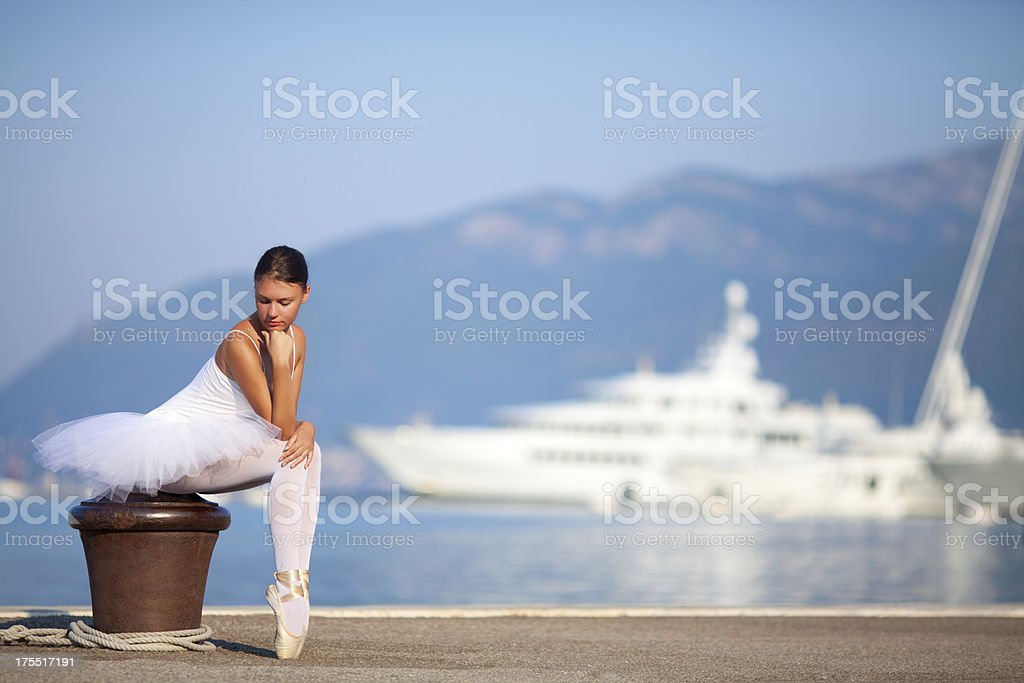 Ballerina sitting and posing in the port stock photo