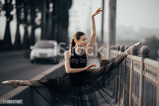 Ballerina sitting in twine pose in a black transparent dress on the bridge against the background of car and road.