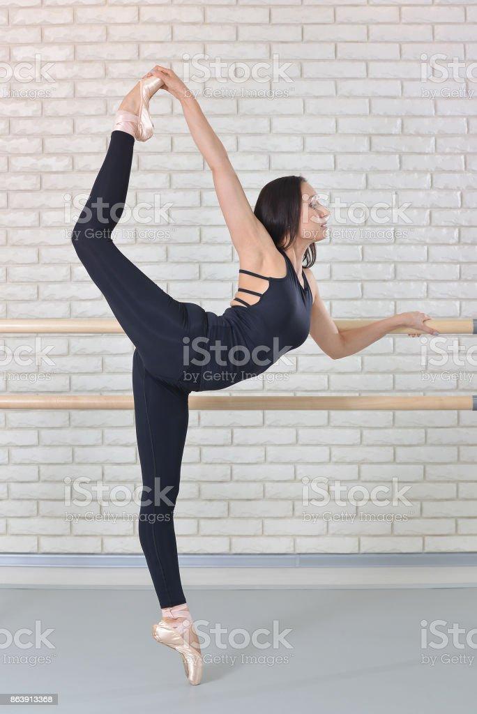 Bailarina se extiende a sí misma junto a la barra en estudio de ballet, bellas mujeres en Body negro practicando ballet. - foto de stock