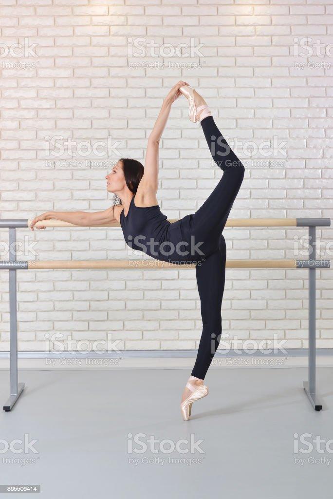 Bailarina se extiende a sí misma junto a la barra en estudio de ballet, bailarín de bellas mujeres practicando ballet. - foto de stock