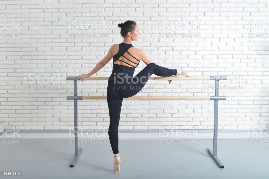 Bailarina se extiende a sí misma junto a la barra en estudio de ballet, retrato de longitud completa. - foto de stock
