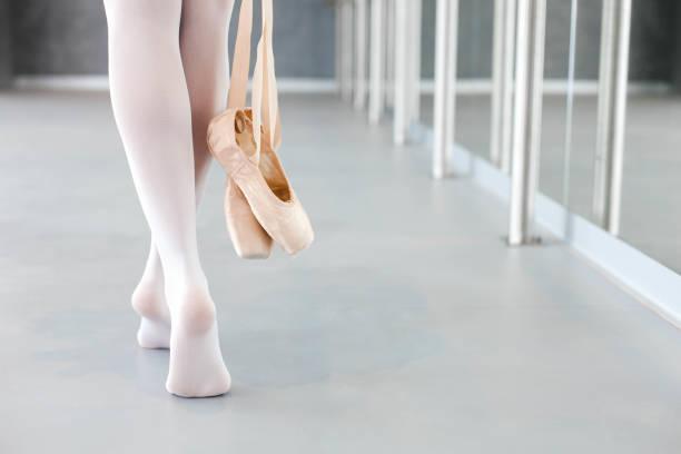 Ballerina takes off ballet pointe shoes. Girl is finishing workout and going barefoot in dance class room. Close up of legs. stock photo