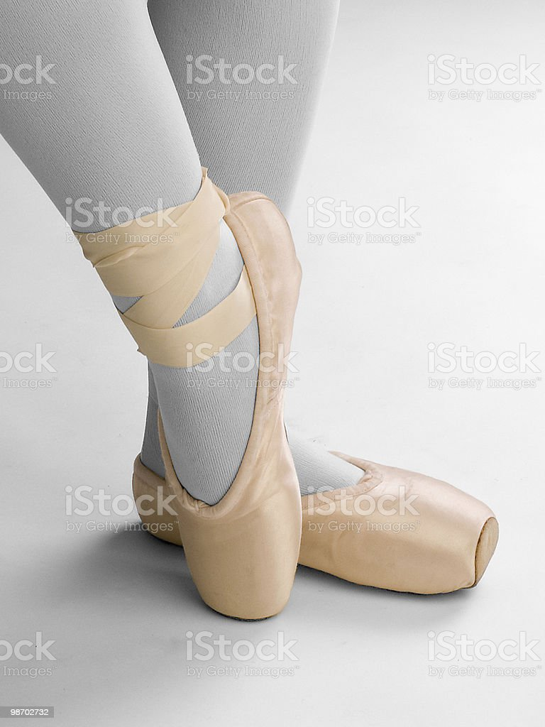 Ballerina wearing gold pointe shoes, at rest royalty-free stock photo
