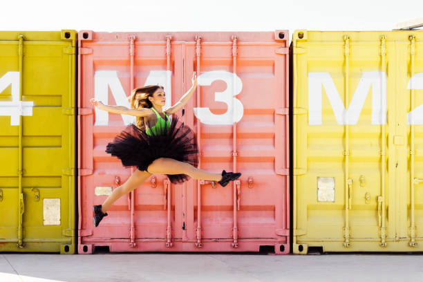 Ballerina with tutu jumping in front of some containers stock photo