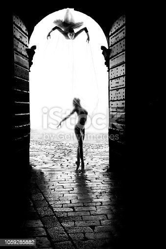 Spider woman trying to attack the ballerina in front of the castle gate