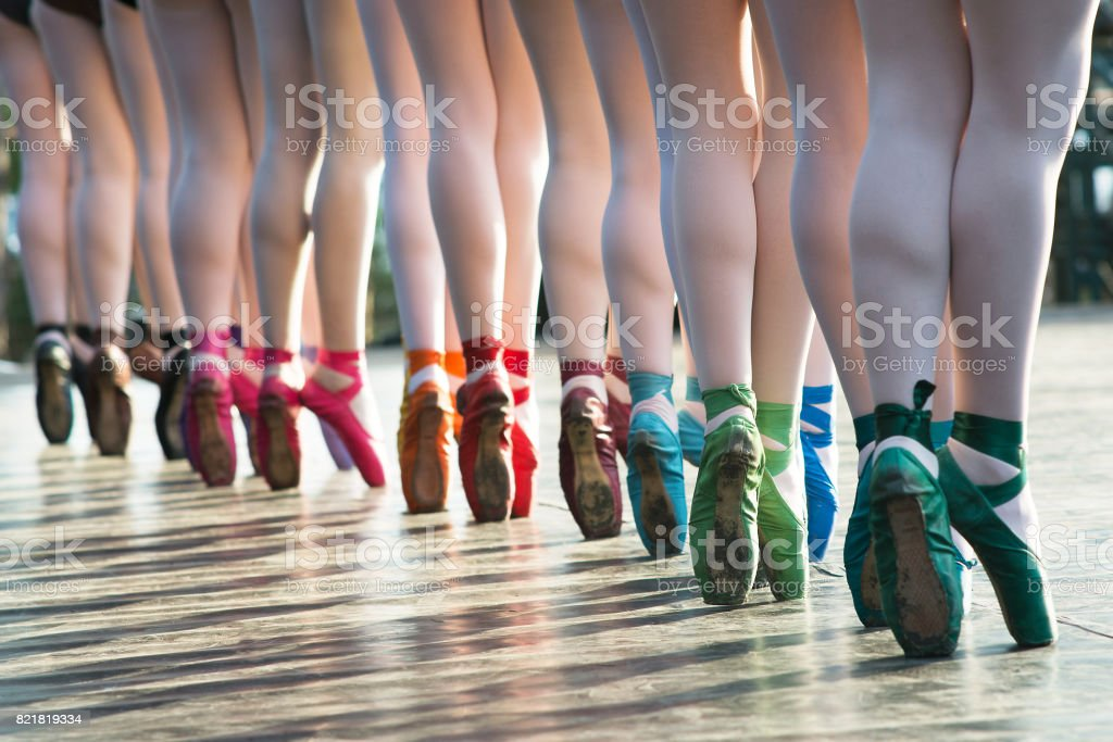 Ballerinas feet dancing on ballet shoes with several colors on stage during a performance. stock photo