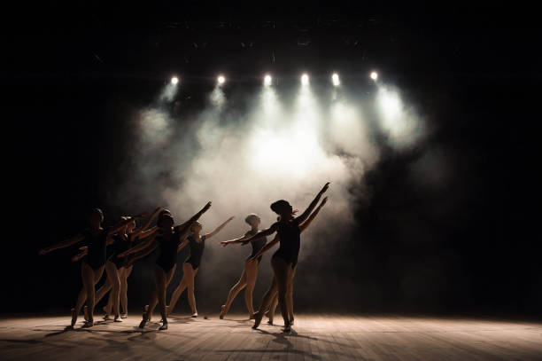 ballet class on the stage of the theater with light and smoke. children are engaged in classical exercise on stage. - turno sportivo foto e immagini stock