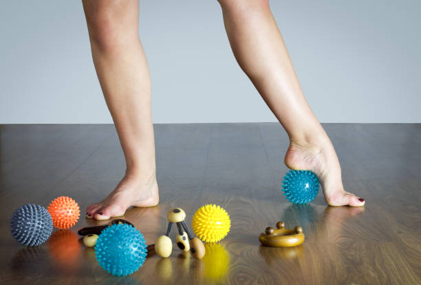 ballet dancer massaging her foot with blue ball for massage ballet dancer massaging her foot with blue ball for massage, wooden floor sole of foot stock pictures, royalty-free photos & images