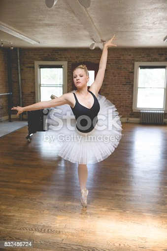 Young female ballerina doing a pirouette in a rustic studio