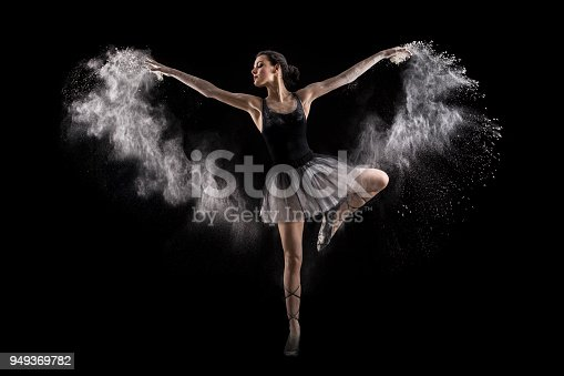 Ballerina dancer performing in cloud of white powder, isolated on black background. About 20 years old, Caucasian brunette.