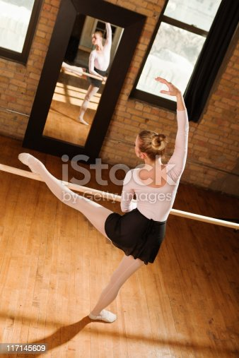 Subject: Vertical view from a tilted high angle, behind a ballet dancer. She is stretching and practicing a dance position in front of a mirror using a dance studio barre rail. Her figure, with outstretched working leg and arm arched over her head, reflects in the mirror. The ballet studio has old wooden flooring, brick walls, and large windows. The dancer is dressed in a pink leotard, black skirt, and ballet slippers, and has her blond hair pulled back in a bun.