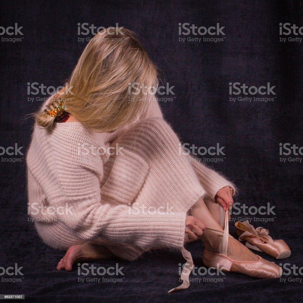 Ballet dancer sitting on the floor and puts on ballet shoes stock photo