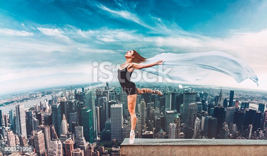 Female ballet dancer tiptoes on the edge of a roof top in New York City. She holds on to a cloth that the wind moves.
