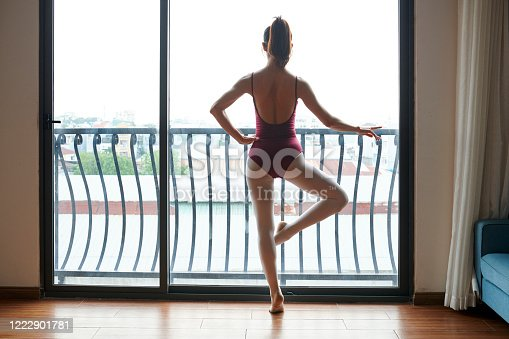 Slim ballet dancer training at in front of big window when staying home during quarantine period