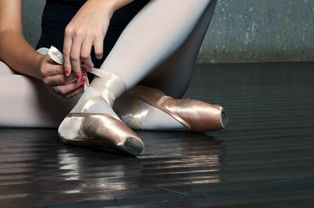 Ballet Dancer Tying on Slippers stock photo