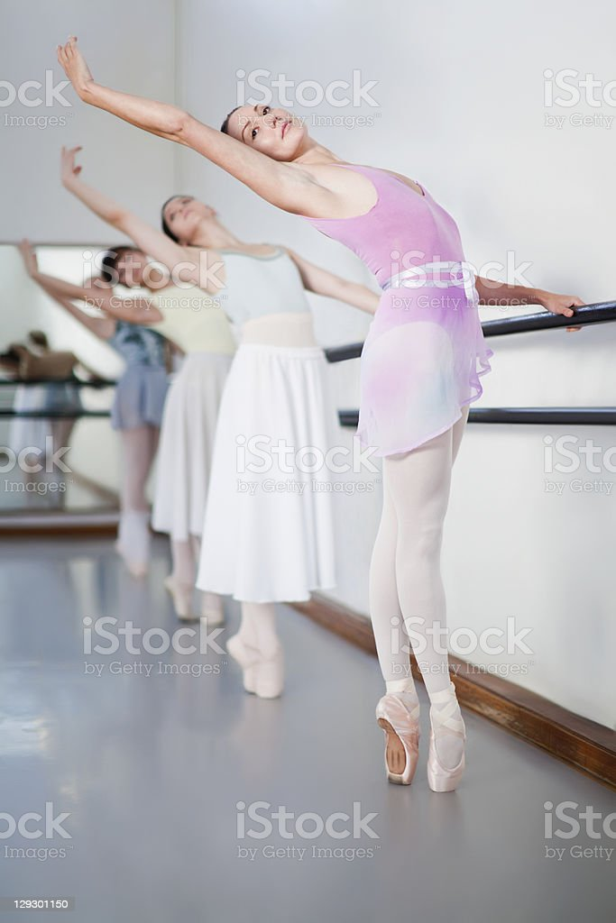Ballet dancers posing at barre stock photo