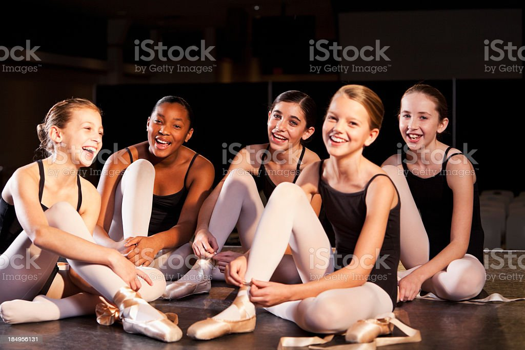 Ballet dancers putting on slippers stock photo