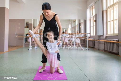 1160198096 istock photo Ballet instructor helping her beautiful dancer stretch 1146994652