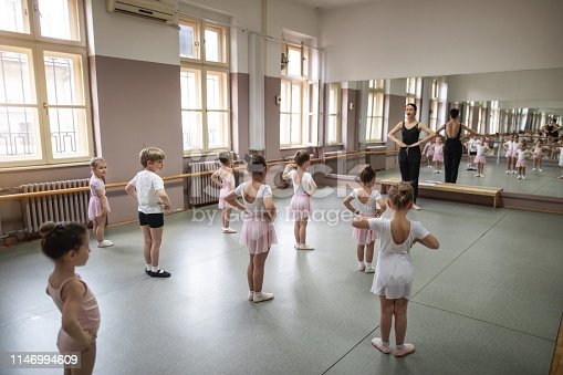 Small girls practicing ballet while following their teacher