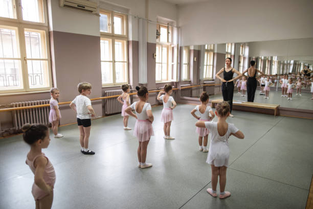 Ballet instructor showing basic steps to a cute group of little girls Small girls practicing ballet while following their teacher dance studio stock pictures, royalty-free photos & images