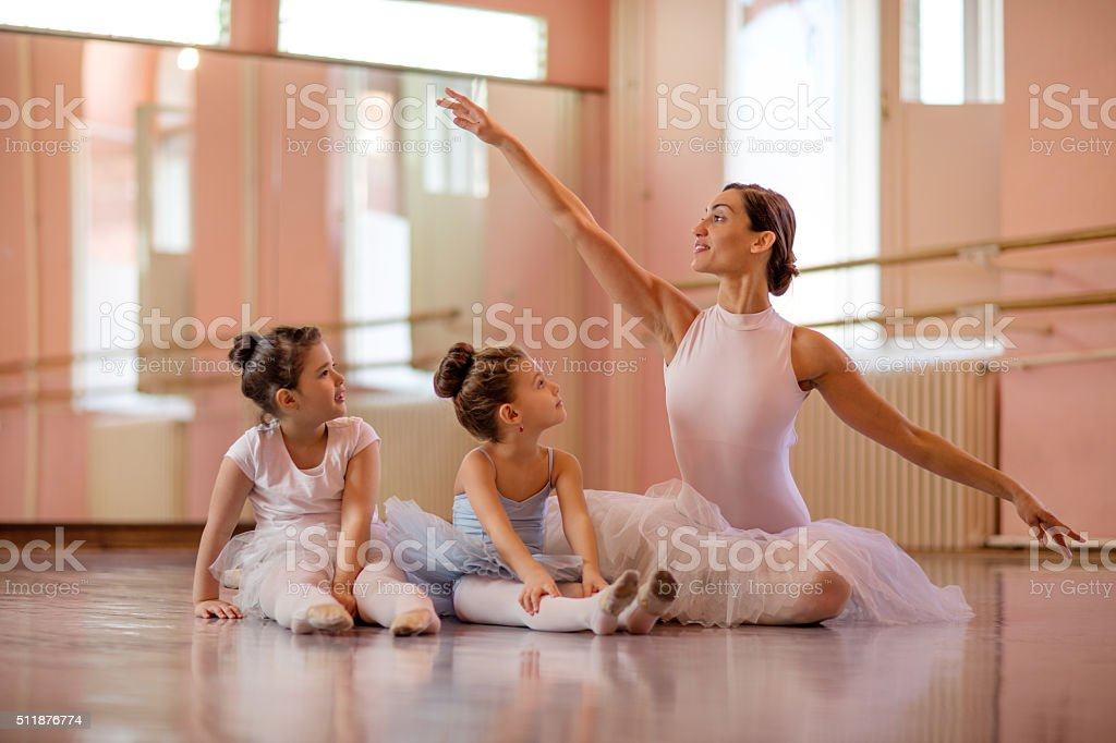 Ballet instructor with two little girls during ballet class. stock photo
