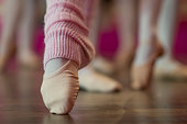 A group of young girls are at ballet practice. The pictures is a close up shot of ballet slippers and leg warmers.