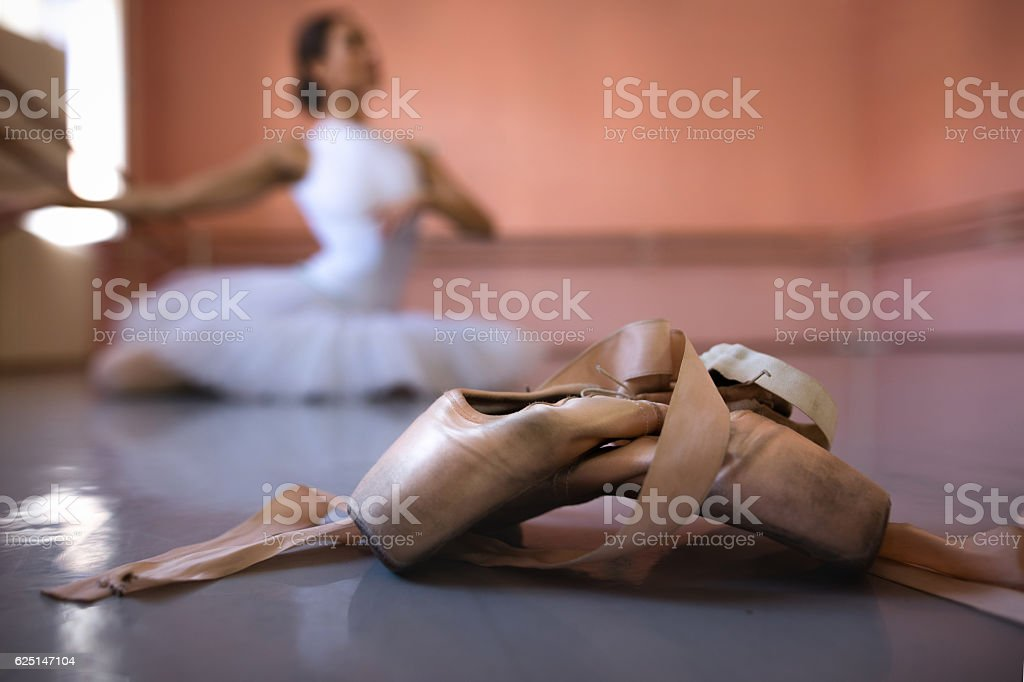 Ballet pumps with ballerina in the background. stock photo