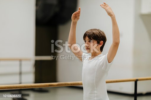 12 years old boy on ballet class in ballet studio.