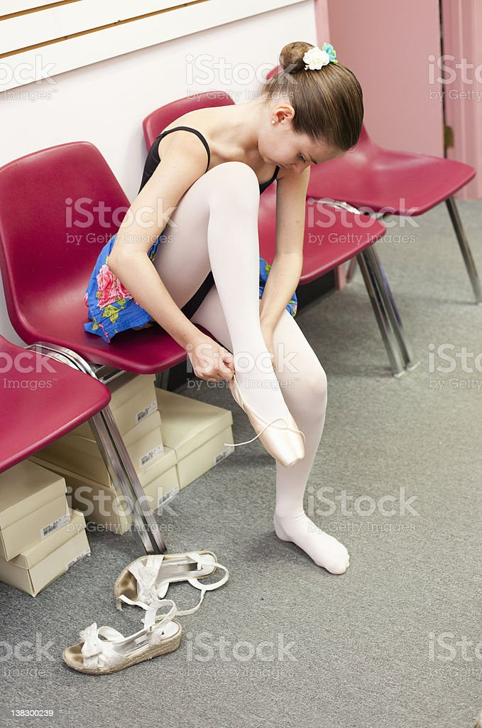 Ballet student tying slippers stock photo