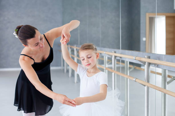 Ballet teacher and little ballerina have practice in dance class. Adult dance trainer is teaching kid girl to do children choreographic exercises. stock photo