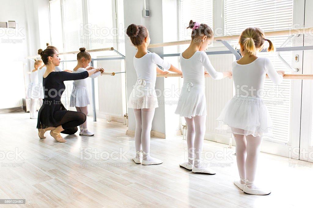 Ballet teacher helping girls with postures during ballet class. stock photo